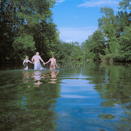 man and two girls wading in