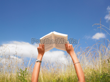 woman reading in field of high