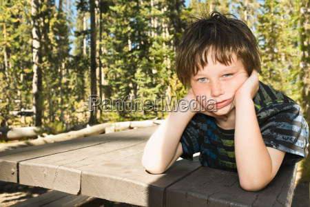 bored boy laying on pier outdoors