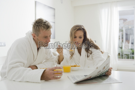 young couple reading paper at breakfast