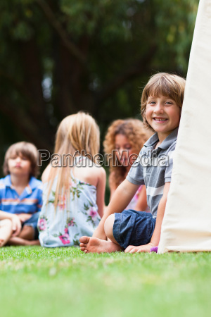 smiling boy sitting in tent outdoors