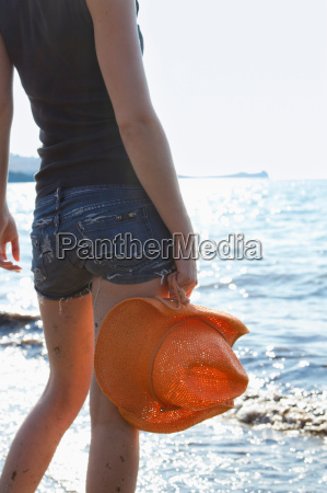 woman carrying sunhat on beach