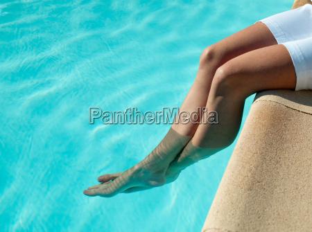 woman dangling her feet in pool