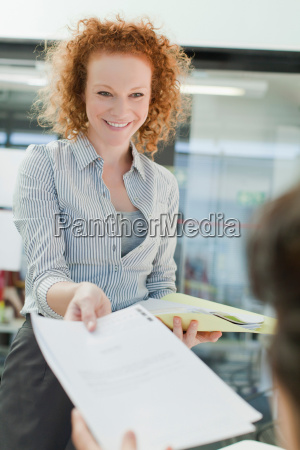 businesswoman turning in report to boss