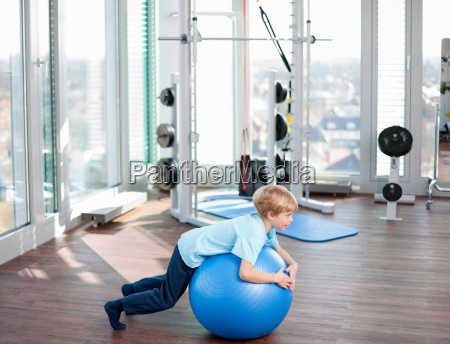 boy playing with exercise ball in