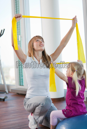 trainer working with girl in gym