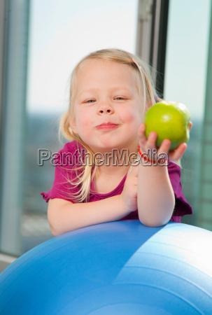 girl eating apple on exercise ball