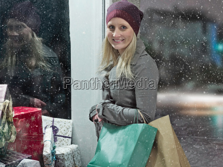 woman carrying shopping bags in snow