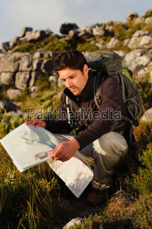 hiker reading map in rocky field