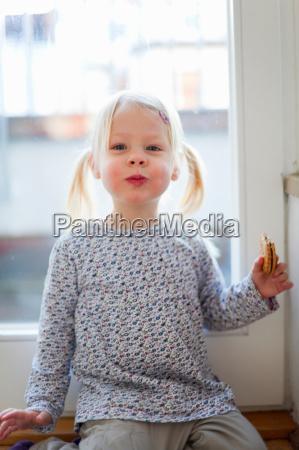 girl eating cookie in doorway