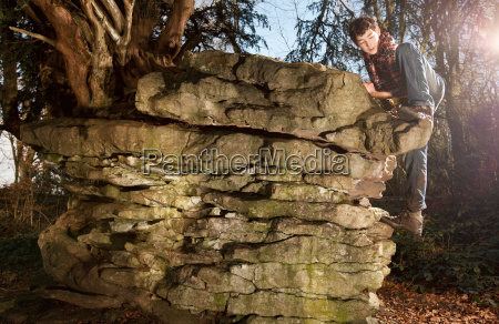 boy climbing rock formations in forest