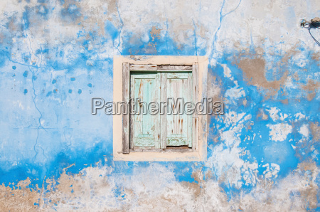 dilapidated window shutters and wall