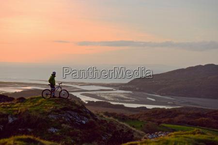 mountain biker standing on hilltop