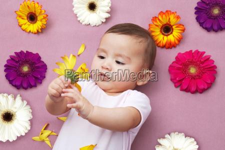 baby girl holding flower