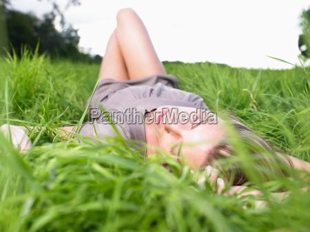 woman resting in a green field