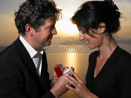 man proposing to woman sunset