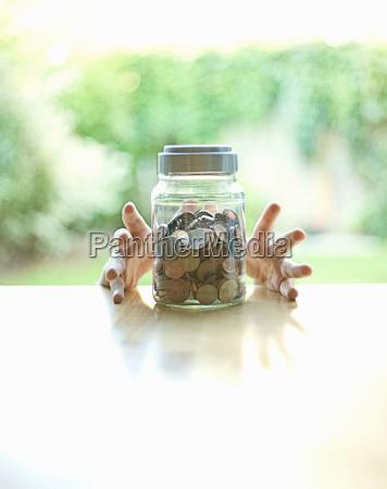hands grabbing jar of change