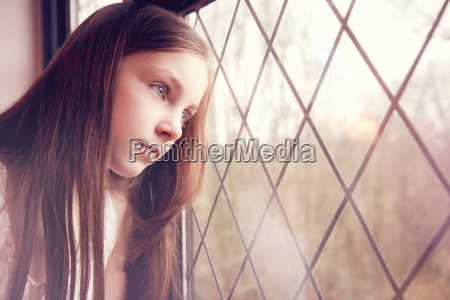 young girl looking though window