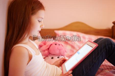 girl using digital tablet in bedroom