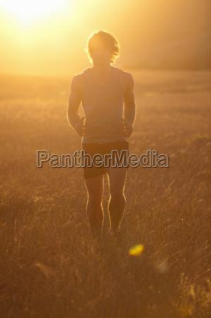 man running in tall grass at