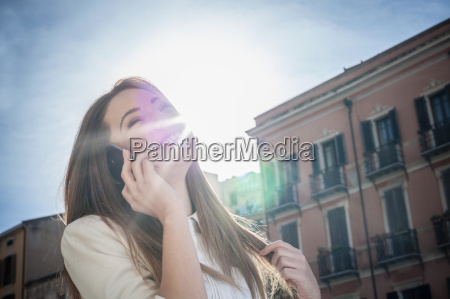 young woman in sunlit street talking