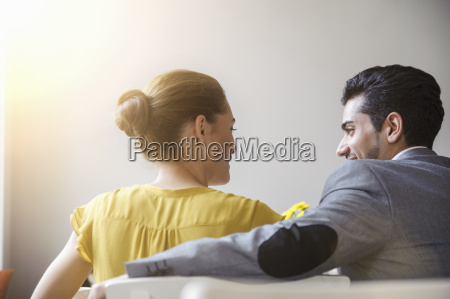 young couple sitting inside cafe rear