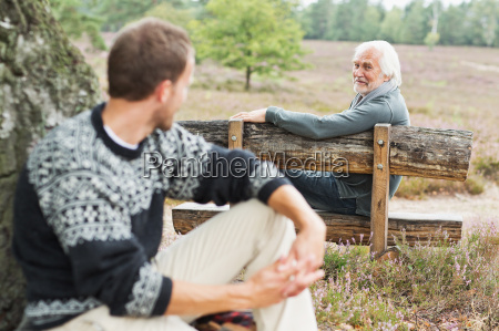 senior man sitting on bench talking