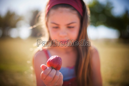 girl eating strawberry outdoors