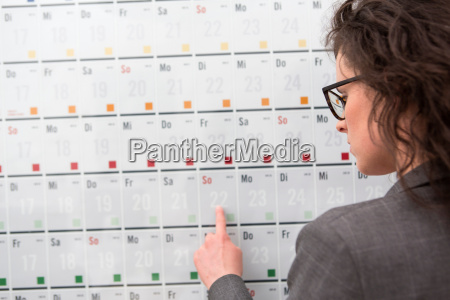 businesswoman pointing to date on calendar