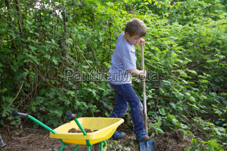 boy digging in garden with toy