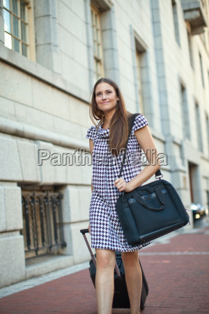young woman pulling wheeled case on