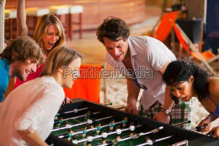 friends having fun playing table football