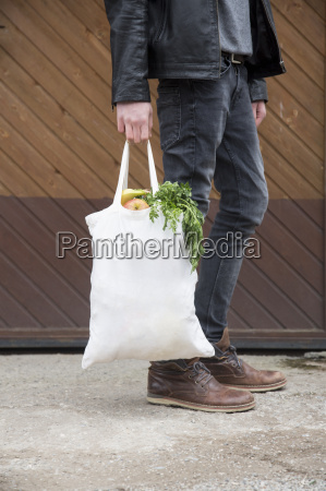 teenage boy carrying reusable shopping bags