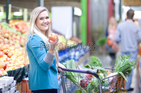 young woman holding apple in indoor