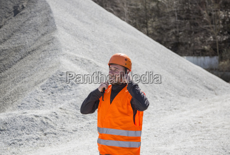 quarry worker fastening helmet at gravel