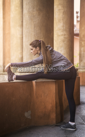 young woman wearing sports clothes stretching