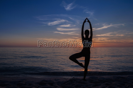 silhouetted young woman in yoga pose