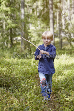 boy walking through forest carrying stick