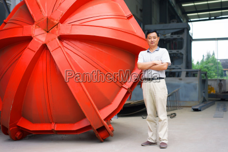 worker standing beside part in crane