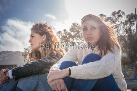 two sullen young women friends sitting