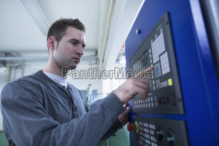 young male technician using control panel