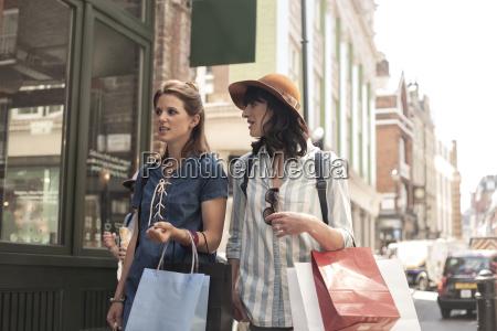 two women carrying shopping bags looking