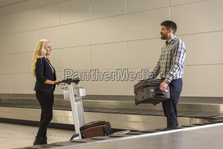 mid adult couple collecting luggage from