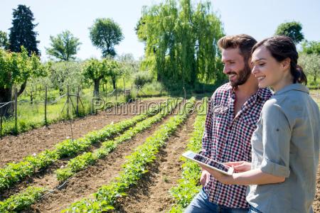 young couple standing in vegetable garden