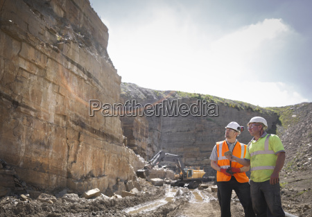 quarry workers inspecting rock strata in