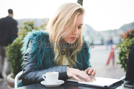 young woman using touchscreen on digital