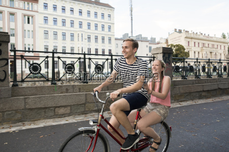young man riding bicycle with young