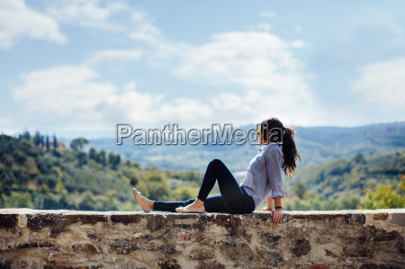 young woman looking out from wall