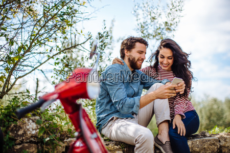 young couple sitting on wall in