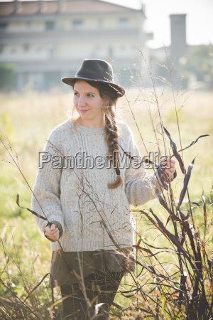 young woman wearing hat touching plants